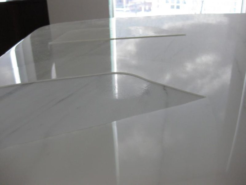 The Acrylic Coating on the Marble Dining Table has come apart and reveals scratches and damage